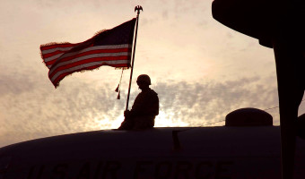 "Master Sgt. Roger Richardson holds an American flag atop a C-130 Hercules, tail number 63-7865, Nov. 13 in Southwest Asia. The aircraft from Ramstein Air Base, Germany, had just flown its last combat mission and will be flown to Davis-Monthan Air Force Base, Ariz., where it will be laid to rest at the ""boneyard."" Sergeant Richardson is a 386th Expeditionary Aircraft Maintenance Squadron flying crew chief. (U.S. Air Force photo/Staff Sgt. Tia Schroeder)"